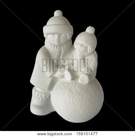 Porcelain figurine depicts children who make a snowman isolated on black. Serial porcelain from the decor store