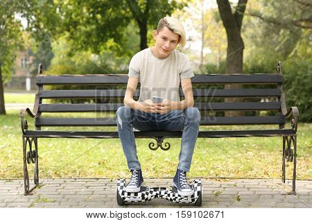 Cute teenager boy sitting on bench in park