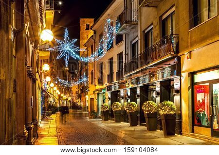 ALBA, ITALY - DECEMBER 07, 2011: Pedestrian street and shops in old town illuminated for Christmas. This area is very popular with locals and tourists visiting Alba for winter holidays.