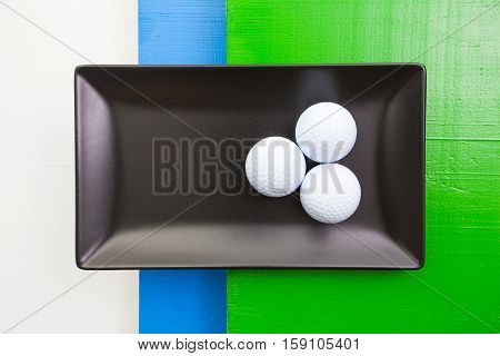 Black ceramic dish with golf balls on over white blue and green wooden table rectangle dish