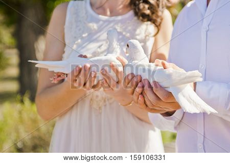 bride and groom holding two white doves in their hands