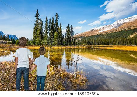 Two boys standing on the shore of a shallow lake. Rocky Mountains on a sunny autumn day. The concept of active tourism