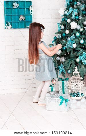 Child girl 4-5 year old decorating christmas tree in room. Holding christmas ball. Wearing trendy gray dress. Celebration.