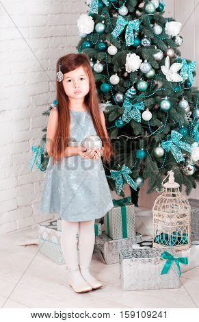 Kid girl 5-6 year old celebrating christmas in room. Holding christmas ball over chritmas tree. Looking at camera. Wearing stylish silver dress. Looking at camera.
