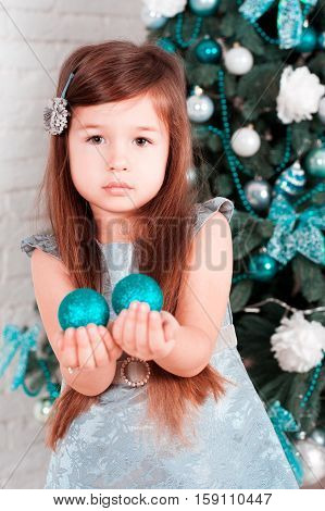Portrait of beautiful girl 4-5 year old with long hair decorating christmas tree in room. Holding christmas balls. Looking at camera. Childhood.