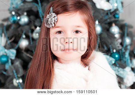 Smiling kid girl 4-5 year old posing over christmas tree in room. Looking at camera. Christmas decoration. Christmas eve. Happy new year. Celebration.