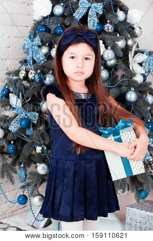 Cute kid girl 4-5 year old holding christmas present over christmas tree in room. Looking at camera. Holiday time. Happy New Year.