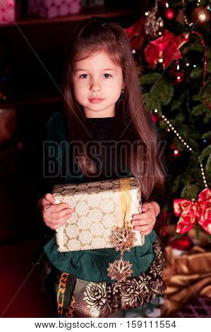 Cute kid girl 3-4 year old holding Christmas present. Looking at camera. Childhood.