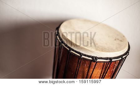 Details of an old wooden djembe in front of white wall.