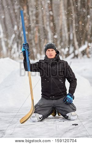 Hockey player poses standing on knees at outdoor skating rink in park.