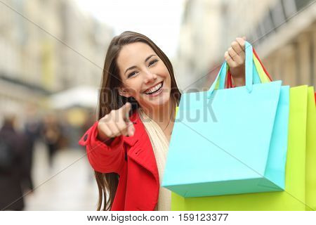 Happy shopper wearing red coat showing blank colorful shopping bags and pointing you in the street