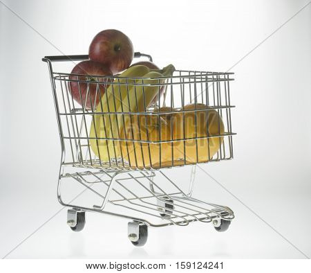 mini shopping cart as a fruit basket or grocery cart holding oranges apples and bananas in front of a gradient white background with reflection viewed from front-right