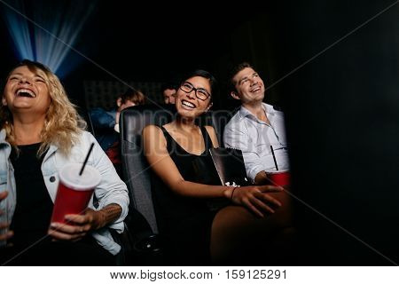 Smiling young woman watching movie with friends in cinema hall. Group of people in movie theater watching comedy film.