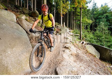 Mountain biker riding on bike in autumn inspirational mountains landscape. Man cycling MTB on enduro trail track. Sport fitness motivation and inspiration. poster