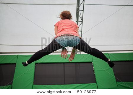 Young woman jumps on trampoline attraction making leg-split, rear view.