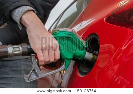 Man Is Pumping Gas In Red Car In Fuel Station.