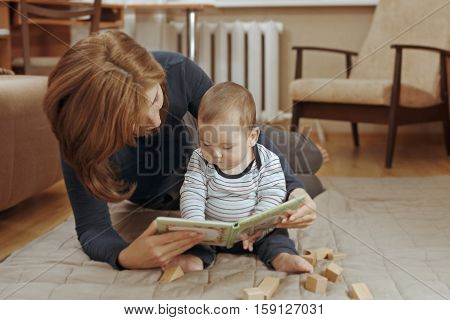 Young Mother Reading A Story To Her Infant Boy