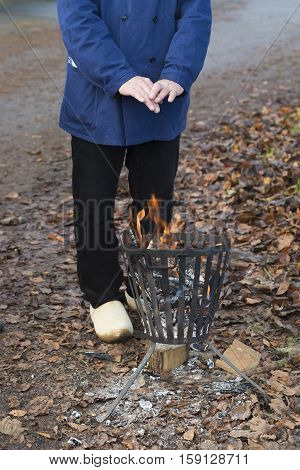 person warming his hands on a metal fire pit