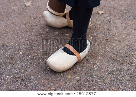woman legs with a pair of pretty new wooden clogs with leather straps