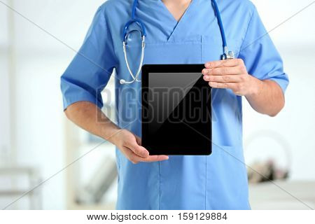 Male doctor with tablet in hands, closeup