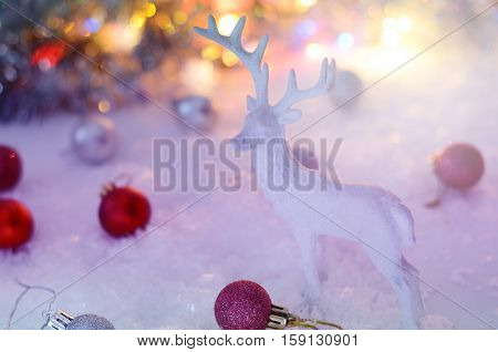 White deer figurines with bright red and white balls against lights of garland. Cozy nordic scandinavian country cottage style. Christmas card template. Winter holiday still life