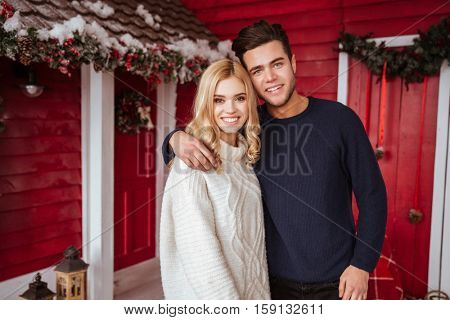 Couple in sweaters near the red house looking at camera.