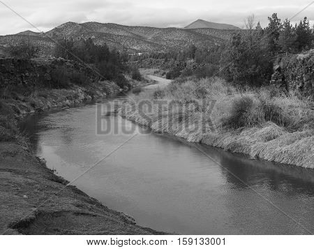 The Crooked River in Central Oregon flows towards the hills on a winter afternoon.
