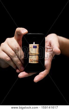 Hands Holding Smartphone showing fifty Euro bill on fire (on black background with very shallow depth of field)