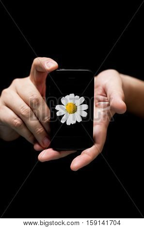 Hands Holding Smartphone showing White Flower (on black background with very shallow depth of field)