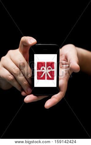 Hands Holding Smartphone showing a Red Gift Box with white ribbon (on black background with very shallow depth of field)