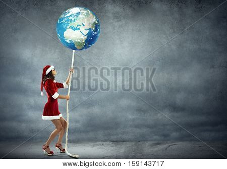 Elegant Santa woman pulling Earth planet on rope