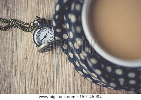 pocket watch on the wooden with coffee cup wrapped in a scarf vintage tone