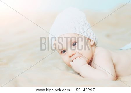 Little Baby Boy In White Hat With Fingers In Mouth