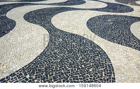 Black and white iconic mosaic, Portuguese pavement by old design pattern at Copacabana Beach, Rio de Janeiro, Brazil