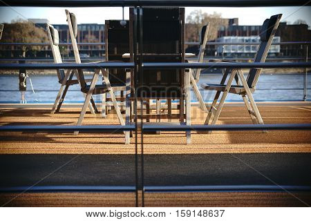 The classy sun deck a passenger ship with a glass reiling carpets tables and chairs.