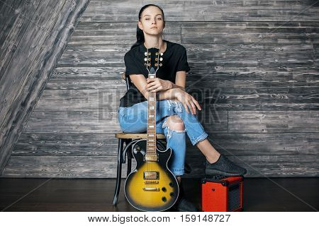 Attractive caucasian female with electric sunburst guitar sitting on amplifier in wooden room. Music concept