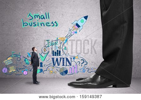 Tiny businessman in concrete room with financial sketch looking at huge competitor. Small business concept