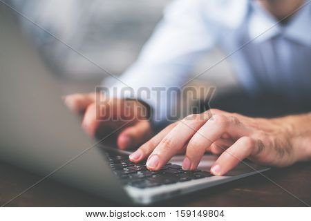 Side view of male hands typing on laptop keyboard