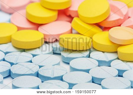 background of blue, yellow and red medical tablets