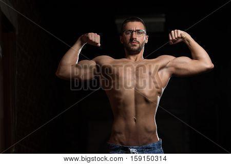 Muscular Geek Man Flexing Muscles In Gym