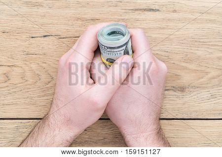Two male hands on an old wooden table and keep a pack of dollars in twisted roll and tapered rubber