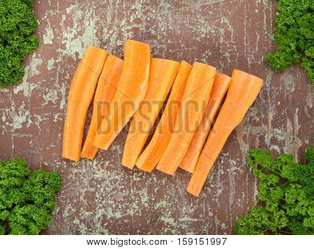 Carrots garnished with green leaves on wooden surface