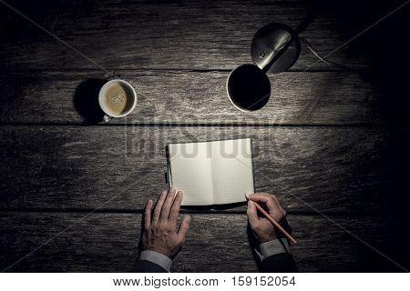 Businessman working late on overtime by the light of a lamp on an old rustic wooden table with a cup of coffee alongside overhead view of his hands writing in a blank journal.