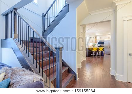 Beautiful living room interior with hardwood floors and vaulted ceiling in new luxury home. View of stairs, and second story loft style area. poster