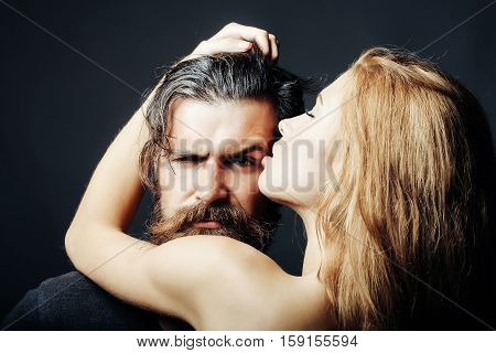 bearded handsome man and female slim flexible body of young pretty sexy woman or girl has long blonde hair embracing