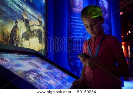 MOSCOW, RUSSIA - AUG 30, 2016: Girl (with model release) listen to audioguide at interactive screen in history park Russia - My History in VDNKh. In expositions of museum modern technology used.