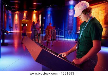 MOSCOW, RUSSIA - AUG 30, 2016: Boy (with model release) touch interactive screen at history park Russia - My History in VDNKh. Professional sound and lighting system at Park enhance effect of dive.