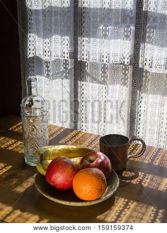 Bowl of fruit empty bottle and copper cup on a table in dappled light coming through a lace curtain
