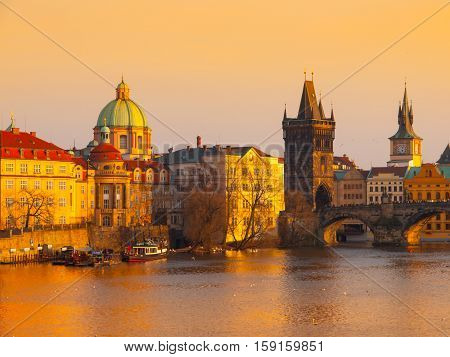 Prague Evening. Towers of Old Town and Charles Bridge over Vltava River illuminated by orange sunset. UNESCO World Heritage Site. Prague, capital city of Czech Republic, Europe