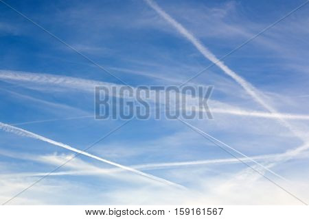Blue sky with contrails and clouds for use as background or for copy or text.